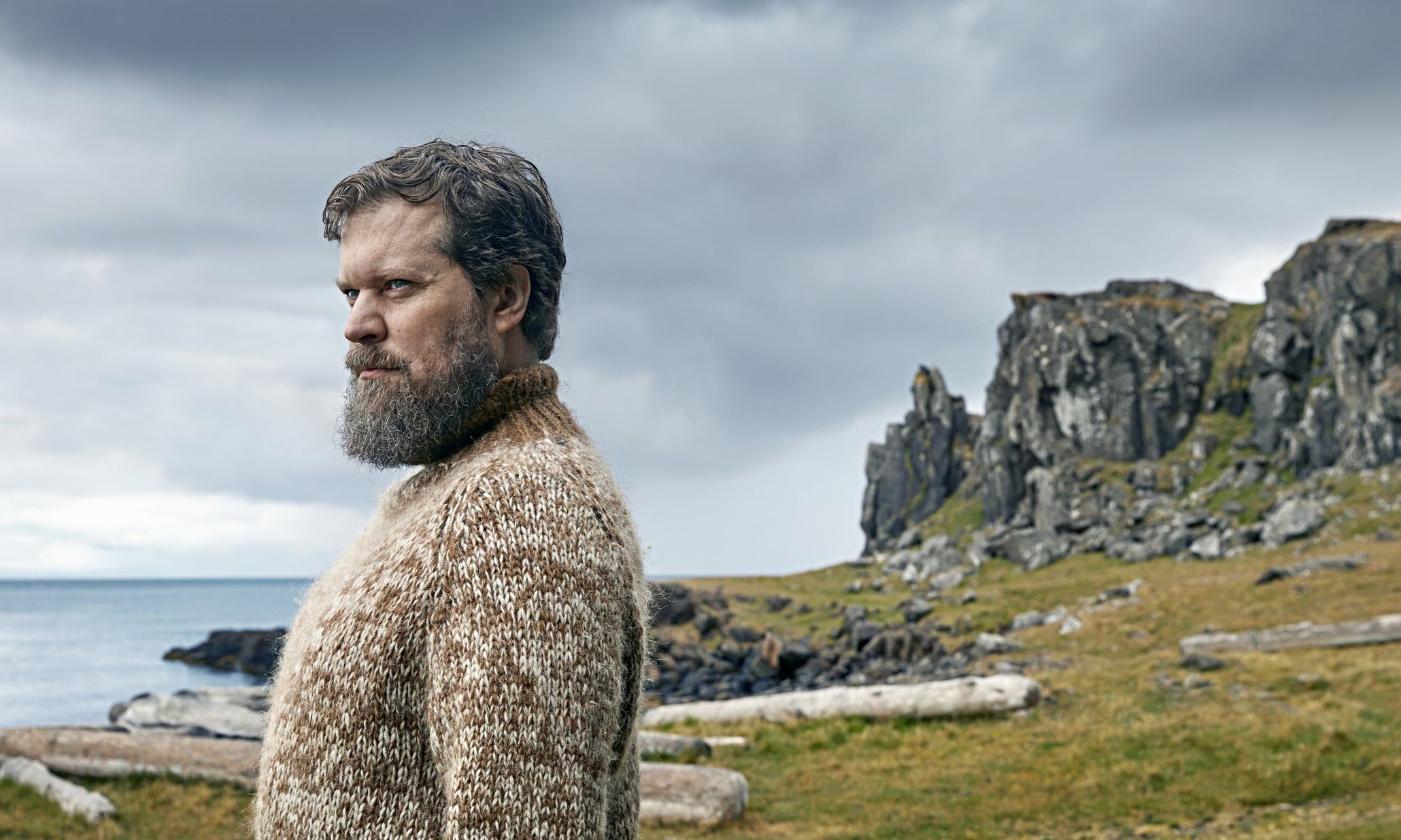 John Grant standing by the sea in Iceland, in a woolly jumper